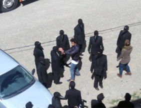 Vestidos de negro y encapuchados